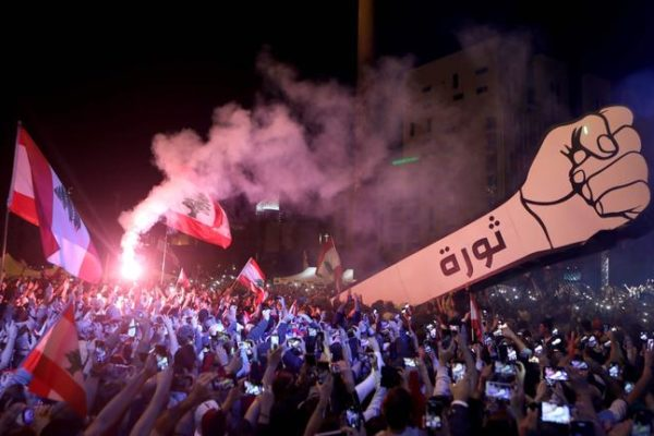 "Lebanese demonstrators raise a new giant sign of a fist that bears the Arabic word ""revolution"" on it, in the Lebanese capital Beirut's Martyr's Square on November 22, 2019, after the sign was burnt overnight by unknown perpetrators. - Lebanese celebrated 76 years of national self-rule Friday, tens of thousands massing for joyous street festivities rather than stiff military parades to hail what a new protest movement calls ""real independence"". (Photo by Patrick BAZ / AFP)"